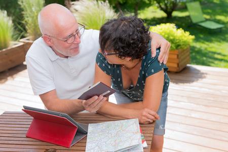 a senior couple preparing vacation trip, outdoors Stock Photo