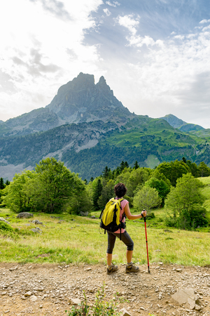 a woman hiker with Pic du Midi dOssau in the French Pyrenees