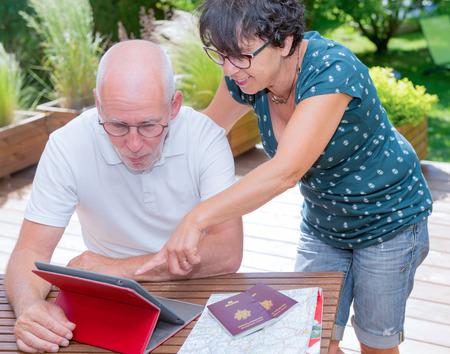 a senior couple preparing vacation trip, on her terrace garden Stock Photo