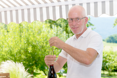 A mature man opening a bottle of red wine