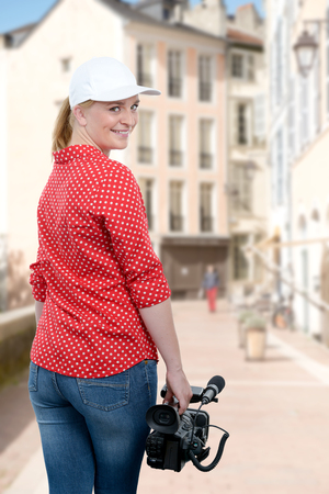 young woman holding his professional camcorder in the street Stock Photo