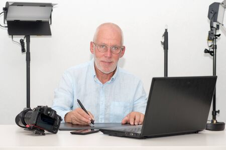 mature man working on his graphics tablet and laptop Imagens