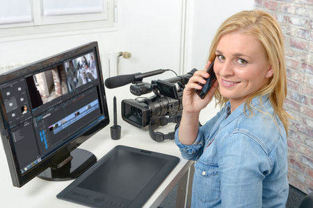young blond woman designer using computer for the video editing Foto de archivo