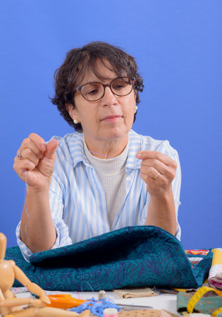 a pretty mature brunette woman sewing patchwork
