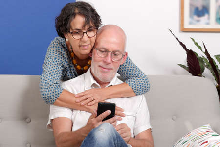 Happy senior couple in love using a smartphone, in their home