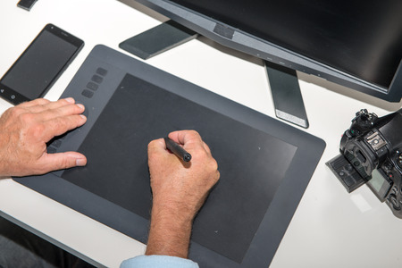 a man working on his graphics tablet, close up of hands Banco de Imagens