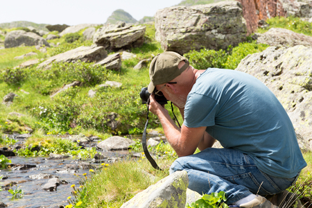 A hiker with camera taking picture of small stream