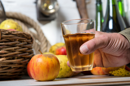aa man with glass of cider, apples at background Stockfoto