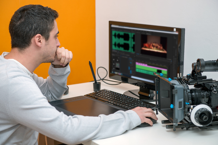 a young man designer using graphics tablet for video editing