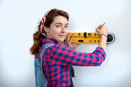a young smiling woman using spirit level