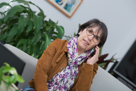 middle-aged woman talking on the phone at home