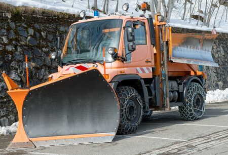 small orange truck using snow plow Stock Photo