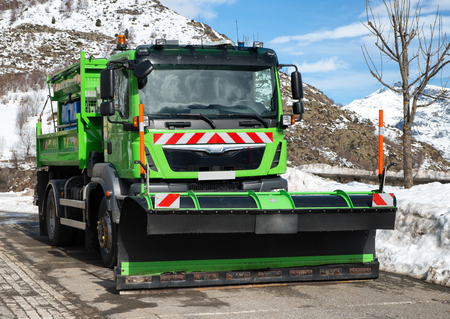 small green truck using snow plow