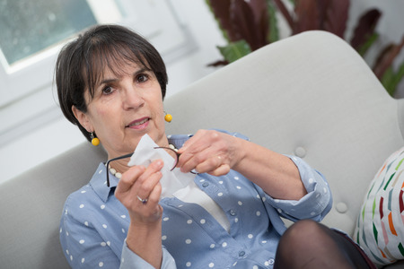 mature brunette woman cleaning her glasses in the sofa