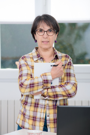 mature woman with a checked shirt in office