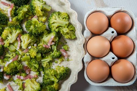 preparation of a quiche with broccoli, eggs and bacon Stock Photo