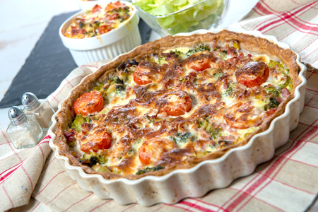 quiche with broccoli, cheese  and tomatoes, on a towel  Stock Photo