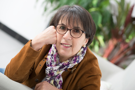 a charming mature woman with brown jacket and glasses Stock Photo