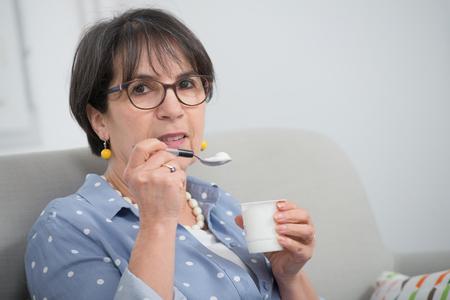 a pretty mature woman eating a yogurt at home Zdjęcie Seryjne
