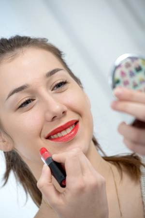 young and smiling woman putting a lipstick
