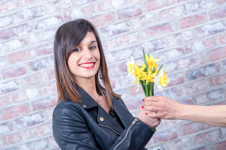 a young brunette woman offers daffodils