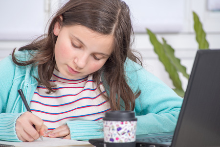a young teenage girl is doing her homework