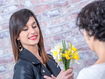 smiling young brunette woman offers daffodils