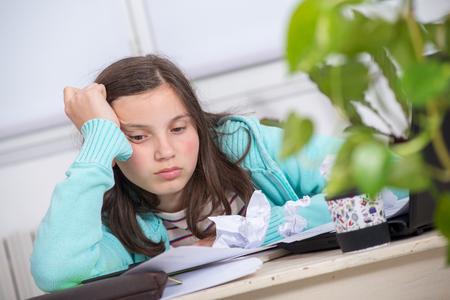 a bored teenage girl is doing her homework