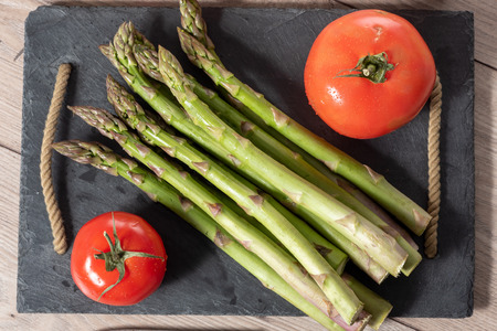 a  bunch of fresh asparagus with tomato on slate plate