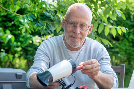 a man repairing a hair dryer for woman Фото со стока - 104041129