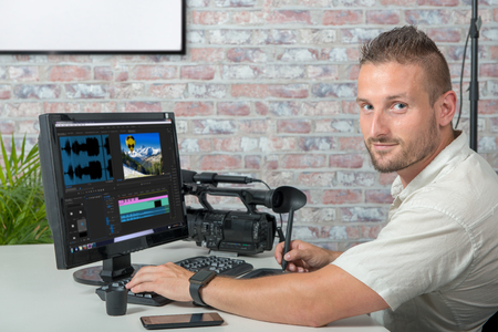 a video editor with computer and professionnal video camera Banque d'images - 105701752