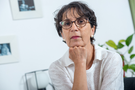a portrait of a beautiful mature woman with eyeglasses at home 写真素材 - 109794078