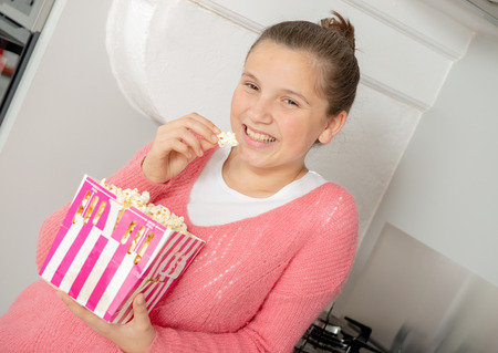 a teenager with a pink sweater eating popcorn
