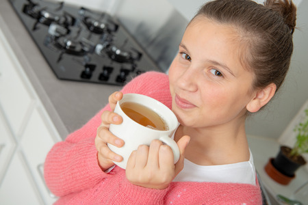 at morning, teenage girl is drinking tea in a bowl