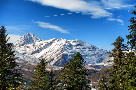 view of fir trees in french pyrenees mountains with Pic du Midi de Bigorre in background Stock Photo
