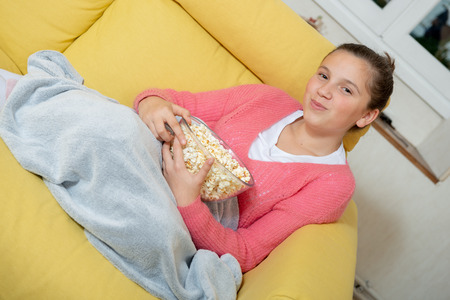 a young teenage girl with pink sweater eating popcorn at home Stock Photo