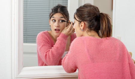 a young brunette woman putting makeup in the mirror