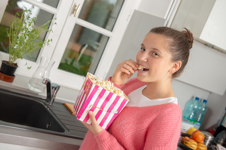 young teenage girl with a pink sweater eating popcorn at home