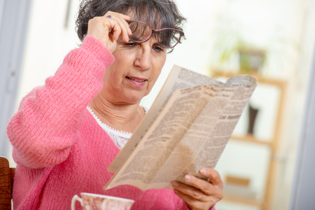 beautiful brunette mature woman dressing in pink reading a newspaper