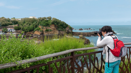 mature woman photographer taking a picture at seaside 版權商用圖片