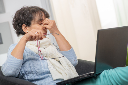 a middle aged woman with stressed out, rubbing her eyes Standard-Bild