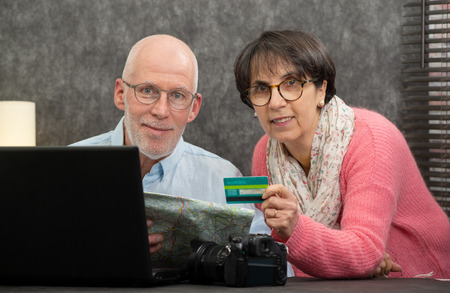 a senior couple making online purchases at home