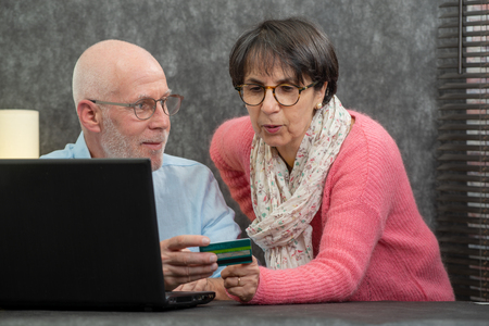 a senior couple making online purchases at home Stock Photo