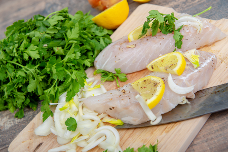 Fresh fish, a raw cod fillets with addition of herbs and lemon Stockfoto
