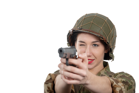 a pretty young woman dressed in ww2 american military uniform with helmet and handgun