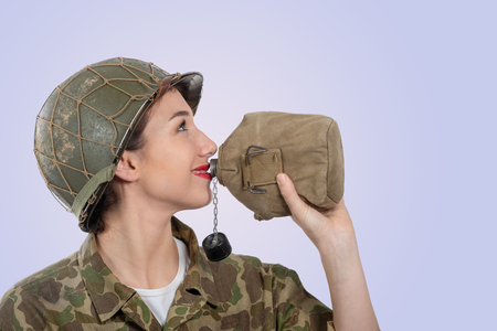 a pretty young woman in ww2 american uniform drinking water Banque d'images