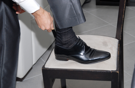 a man groom dressing up with classic elegant shoes