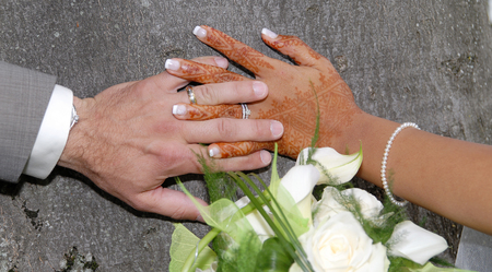 Hands and rings on a wedding bouquet