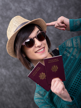 smiling young woman with summer hat holding passports 版權商用圖片