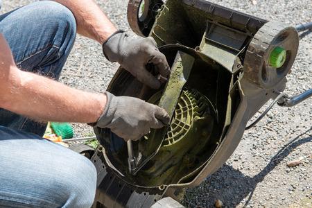 a man repairing an electric lawn mower Foto de archivo